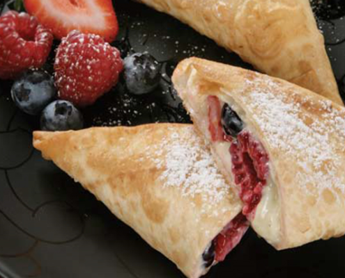 Raspberry-and-blueberry-triangles-with-creamed-cheese-dusted-with-sugar.